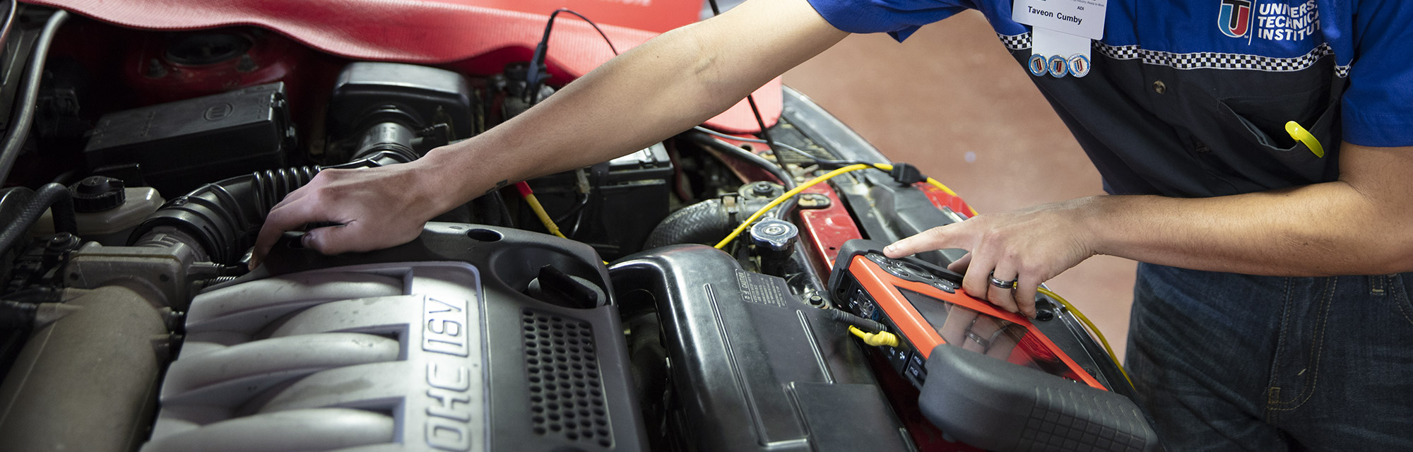 Student using diagnostic tool to test vehicle