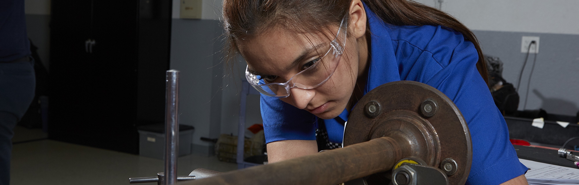 Female student working on car axle.