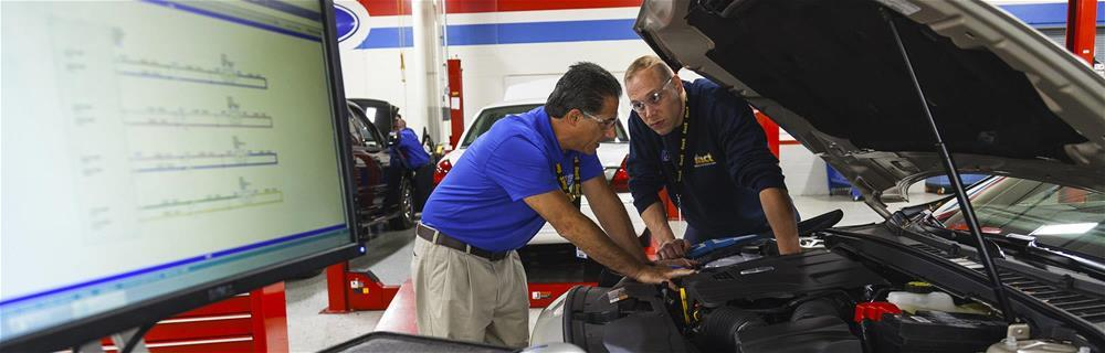 Two students working under the hood of a car at Universal Technical Institute, a trade school for automotive technician and diesel technician training