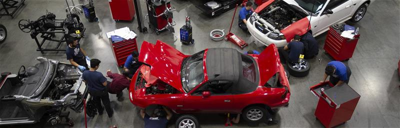 An image of students train to prepare for careers as automotive technicians from Universal Technical Institute working on a bright red car