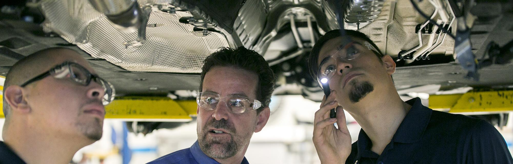 Instructor and students working on an automobile.