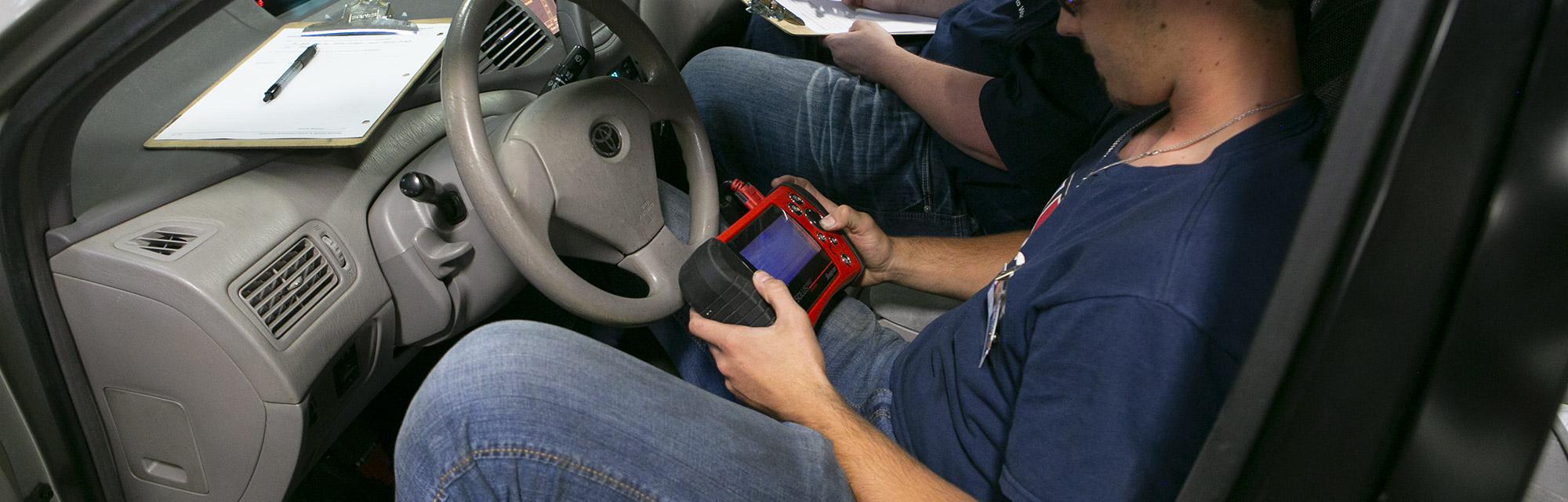 Technician checking diagnostics on automobile