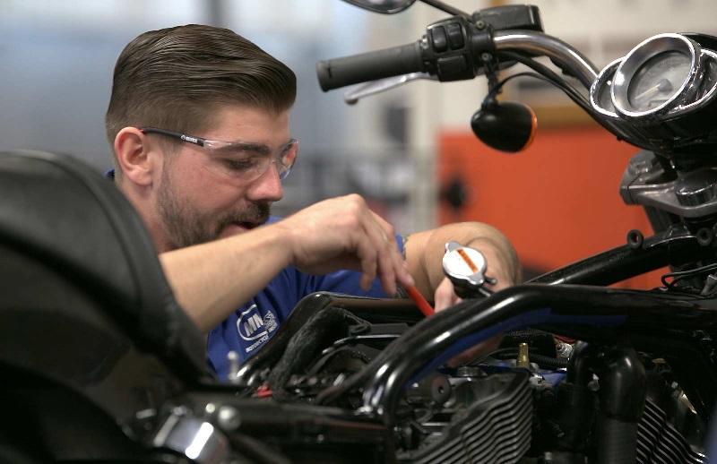 A motorcycle student makes an adjustment to a Harley-Davidson bike in an MMI lab.
