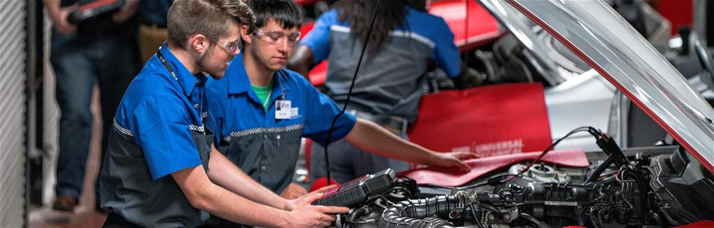 Students working on an engine in an Automotive program lab at Universal Technical Institute