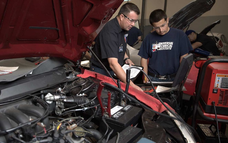 An instructor helps a student check a vehicle's battery in a UTI lab.