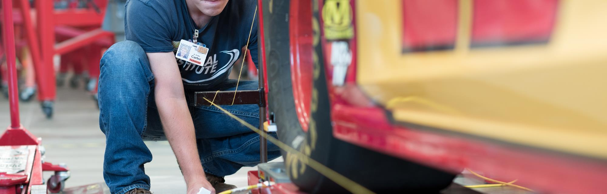 Student inspecting a NASCAR automobile