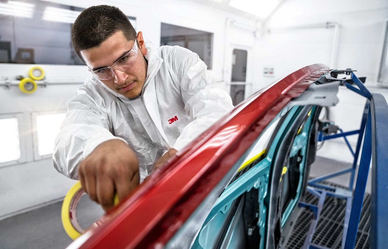 An auto body repair student works on a vehicle in a UTI lab.