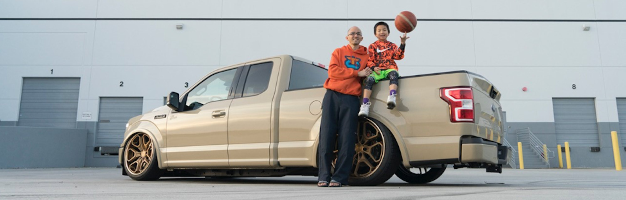 Neil Tjin holding his son next to a Ford truck