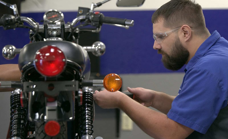 A motorcycle student makes an adjustment to a bike in an MMI lab.