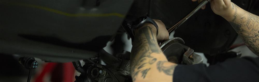 Student tighten screws on a brake drum