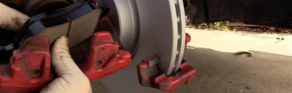 Mechanic changing brake pads on a new rotor.