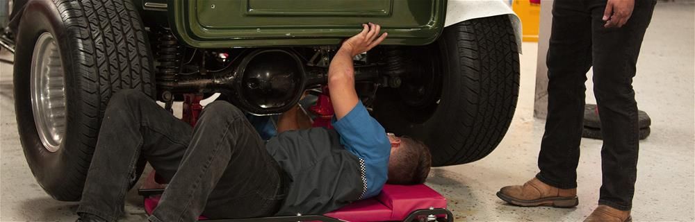 Mechanic looking under a vehicle