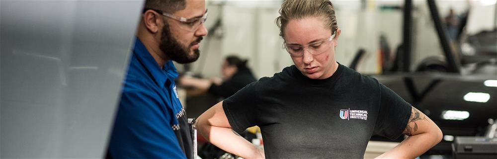 Universal Technical Institute instructor working with a female student in a lab, which is similar to experience that Bogi Lateiner had when she attended UTI in Arizona prior to become a television personality on All Girls Garage on Velocity