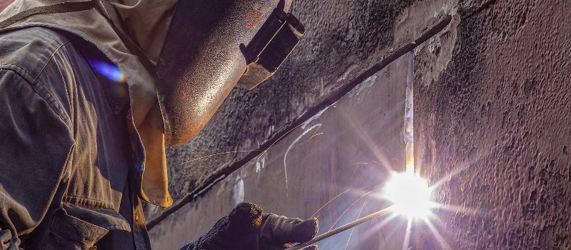 A welder makes repairs to the hull of a ship.
