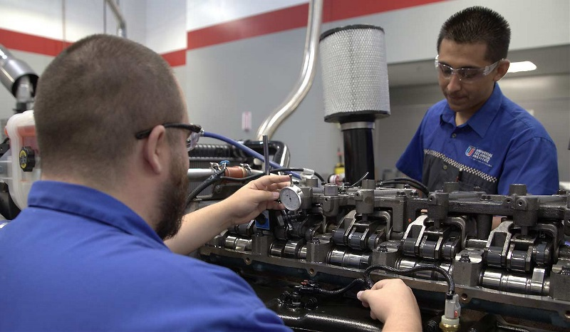 Diesel students work on an engine in a UTI lab.