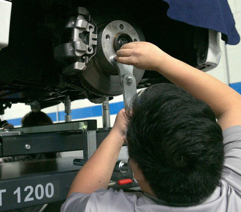 A student adjusts brakes in a UTI Automotive lab.