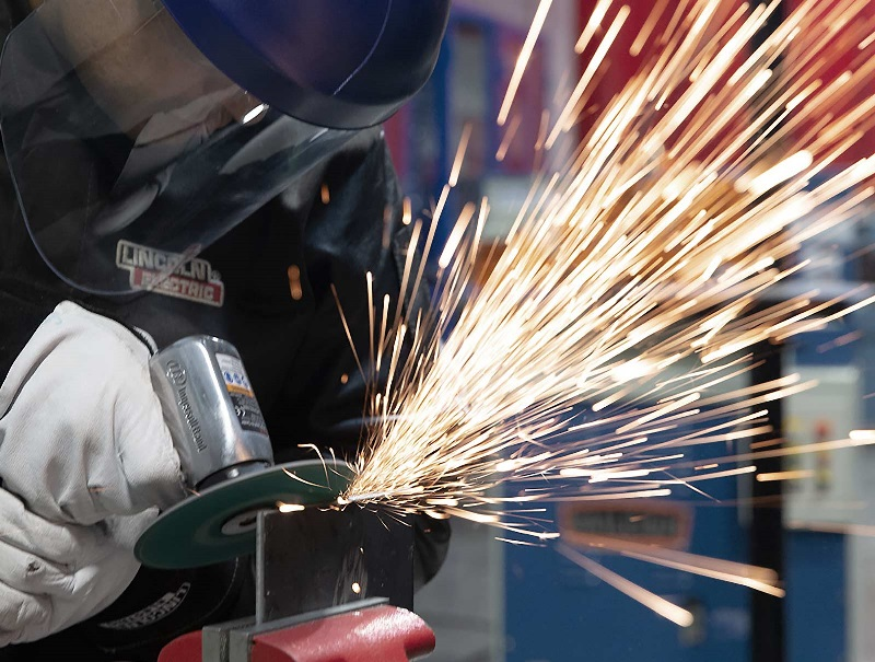A welding student makes a cut on a piece of metal in a UTI lab.
