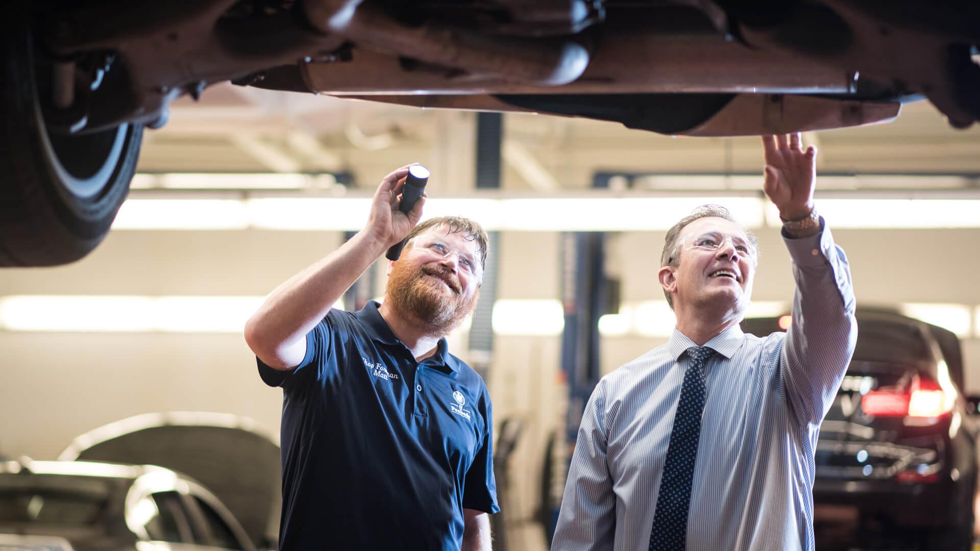 Mechanics Inspecting Under a Car