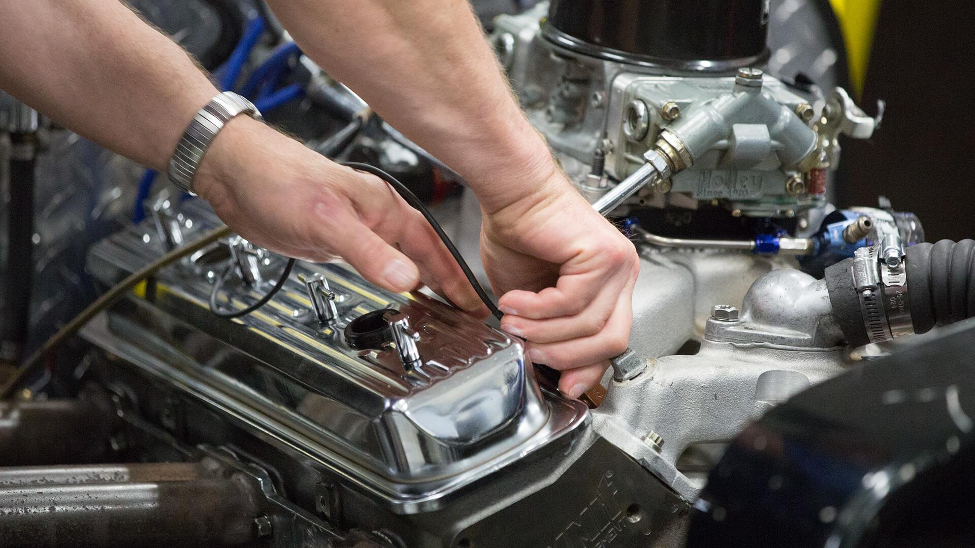 Students hands working on an engine