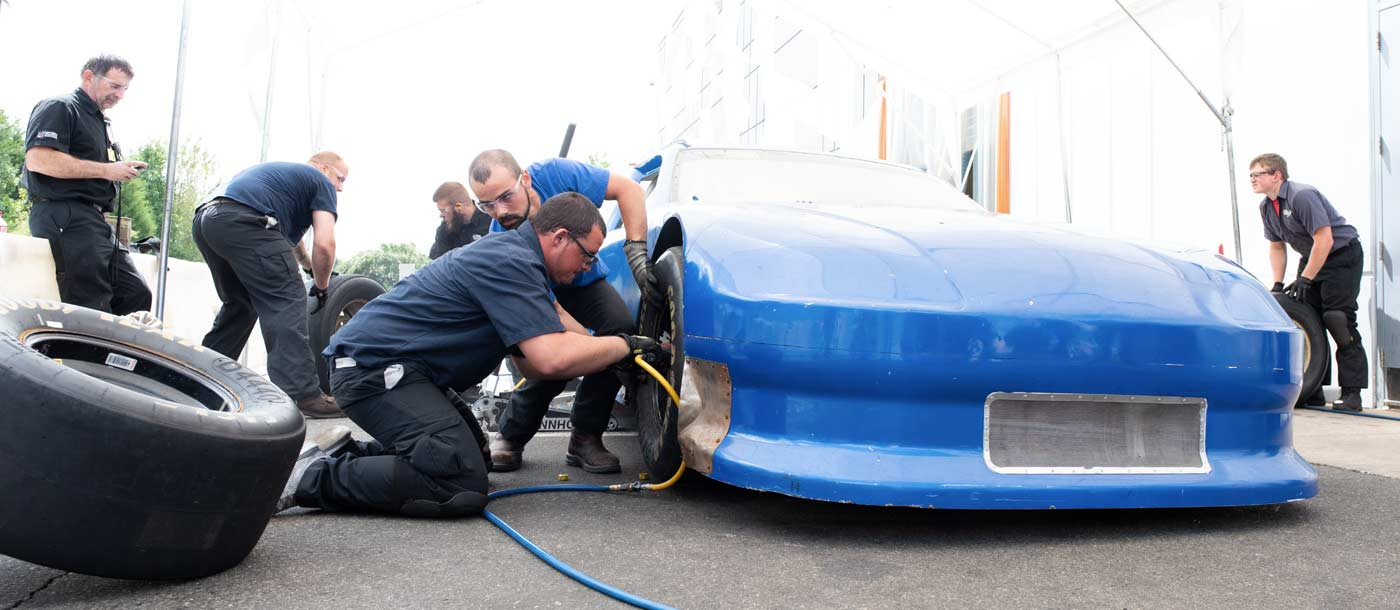 An image of students changing a tire at NASCAR Technical Institute in Mooresville, North Carolina