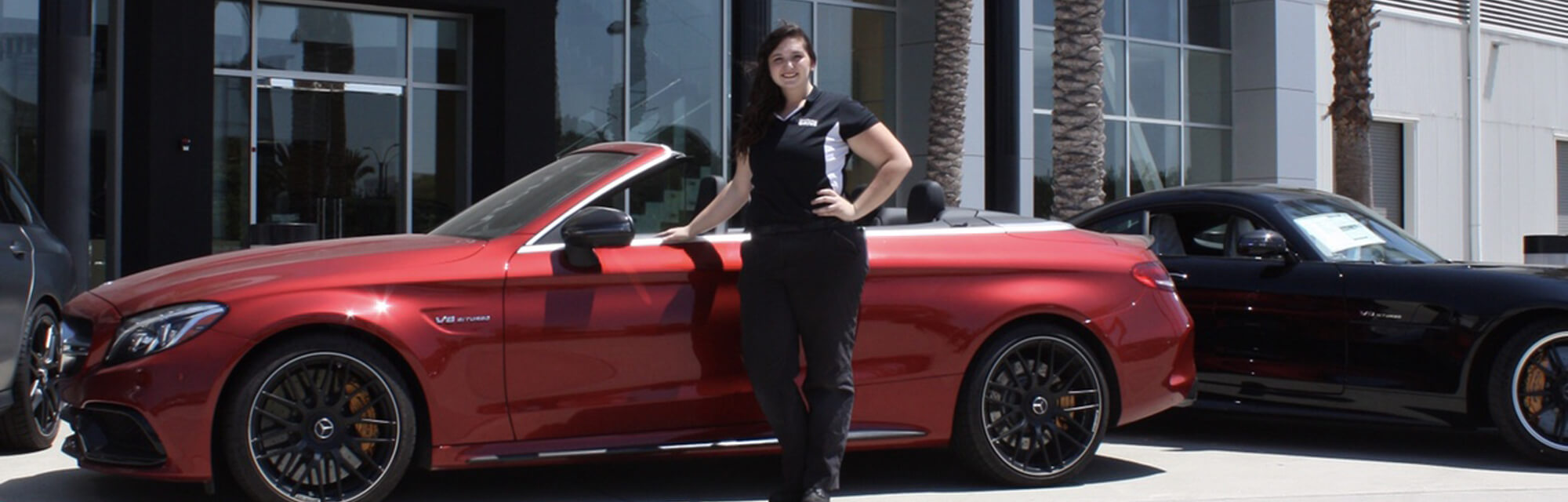 UTI graduate Veronica Anderson standing next to a red Mercedes-Benz convertible, and she also graduated from the Mercedes-Benz DRIVE Program at UTI Long Beach