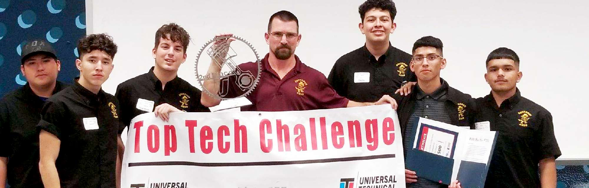 An image of a Universal Technical Institute instructor with students from the Top Tech challenge