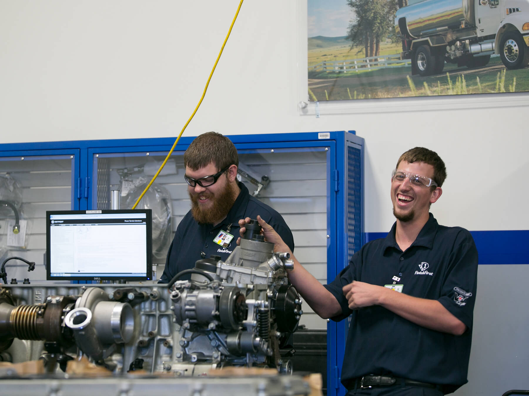 Daimler students laughing while working on an engine at Avondale Campus
