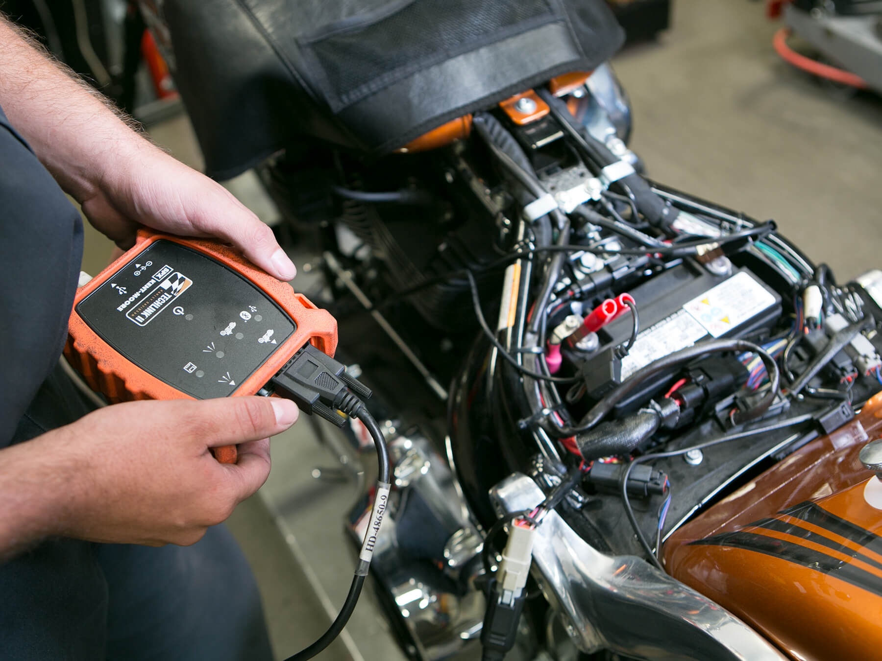 MMI instructor holding an orange and black tool hooked into a motorcycle