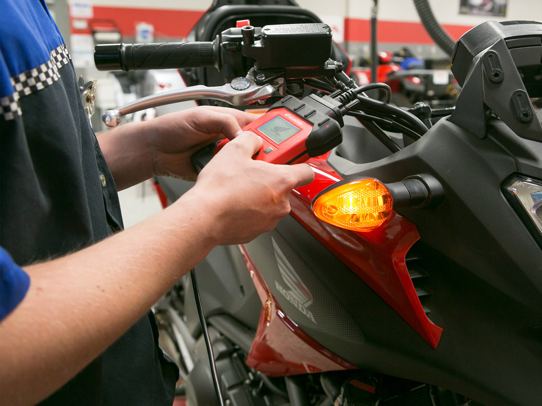 MMI student holding a red Honda tool hooked into a red Honda motorcycle