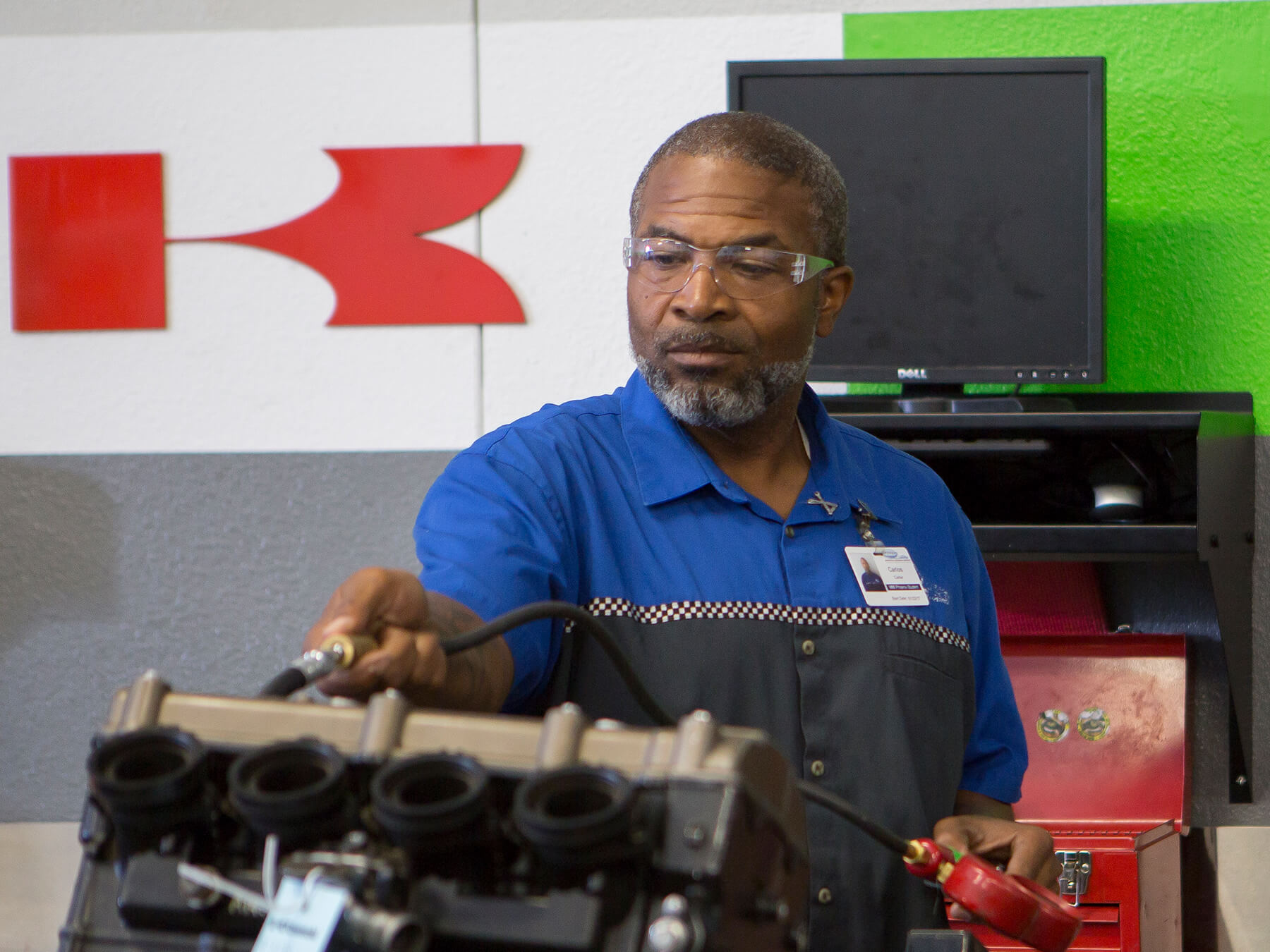 MMI instructor working on an engine in the Kawasaki Moto lab