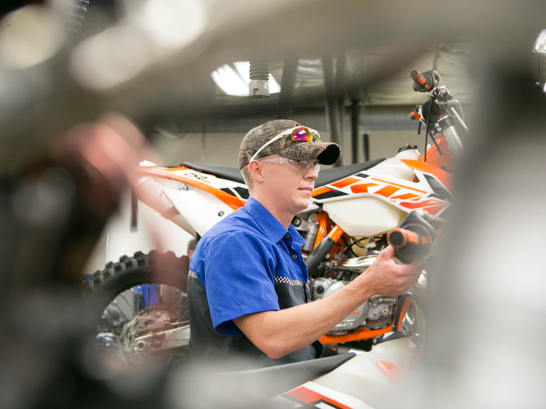 MMI student looking at an orange KTM motorcycle