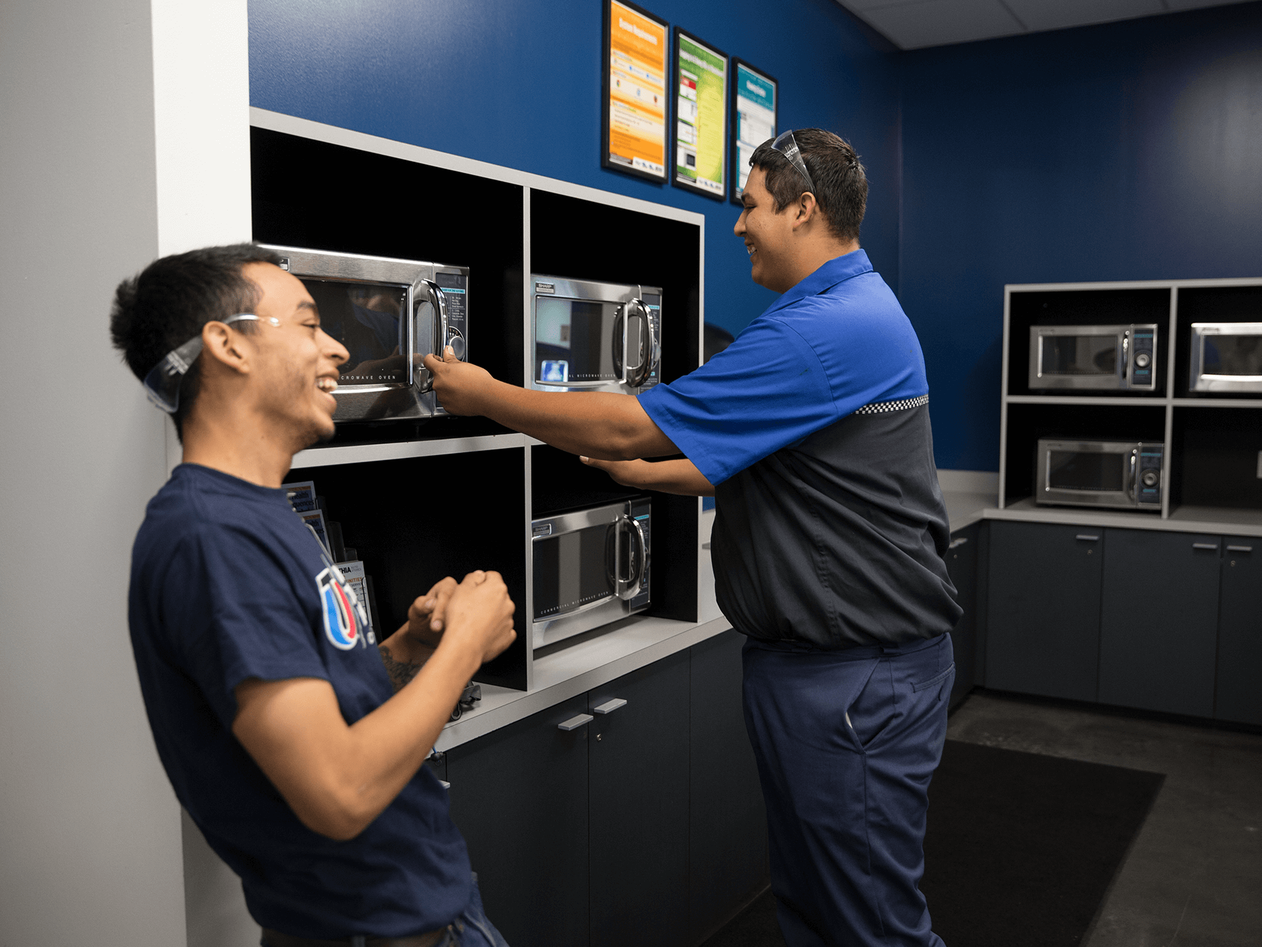 Students laughing near a microwave in the break room at Long Beach campus