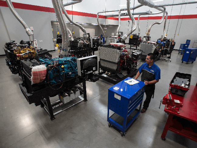 Student walking with a Snap On toolbox in-front of Diesel Engines at Long Beach campus