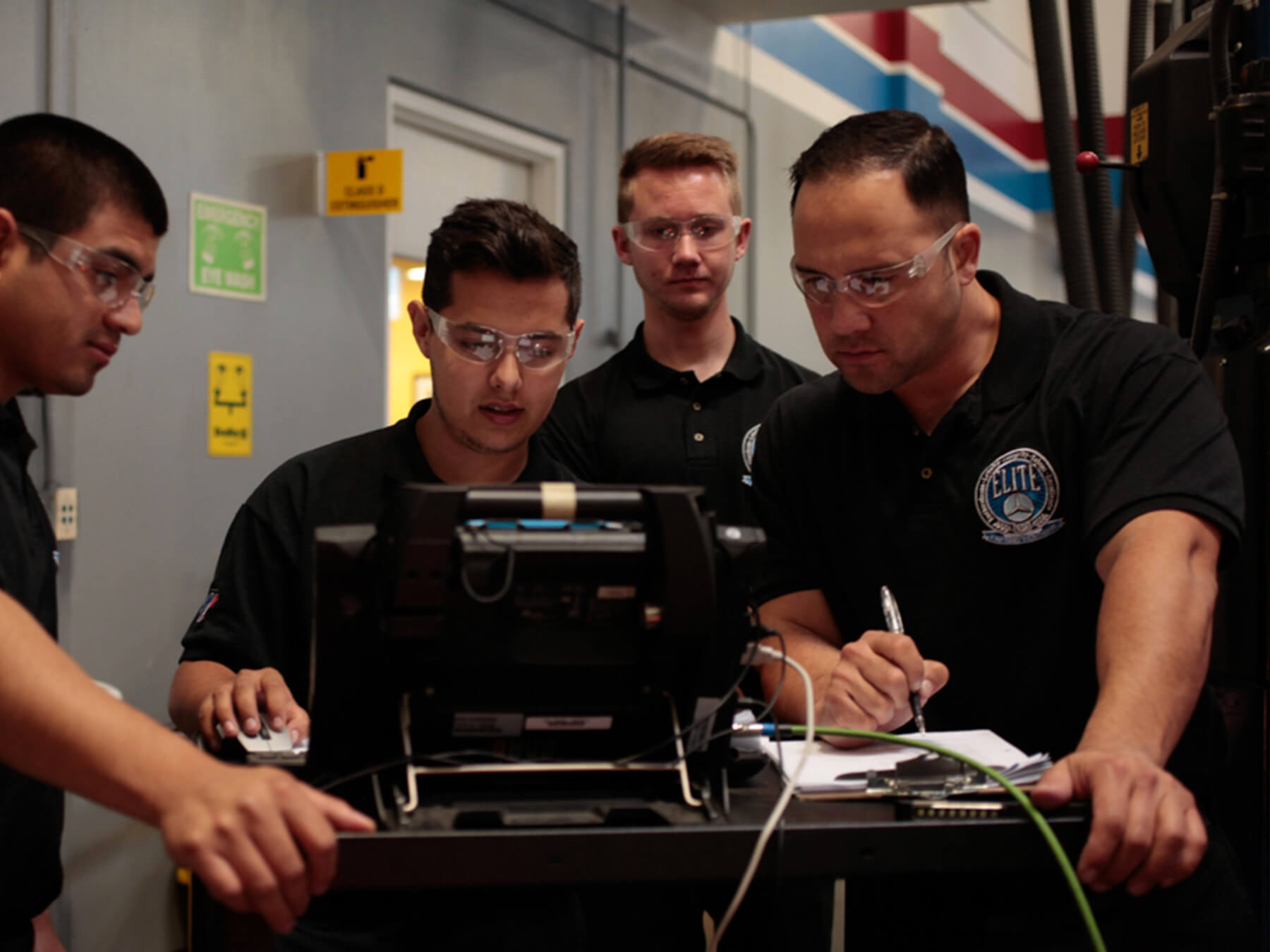 UTI students looking at a computer in auto lab