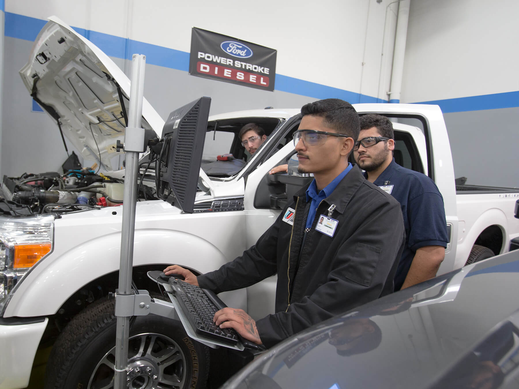 UTI students working on a truck while looking at a computer in the ford auto lab