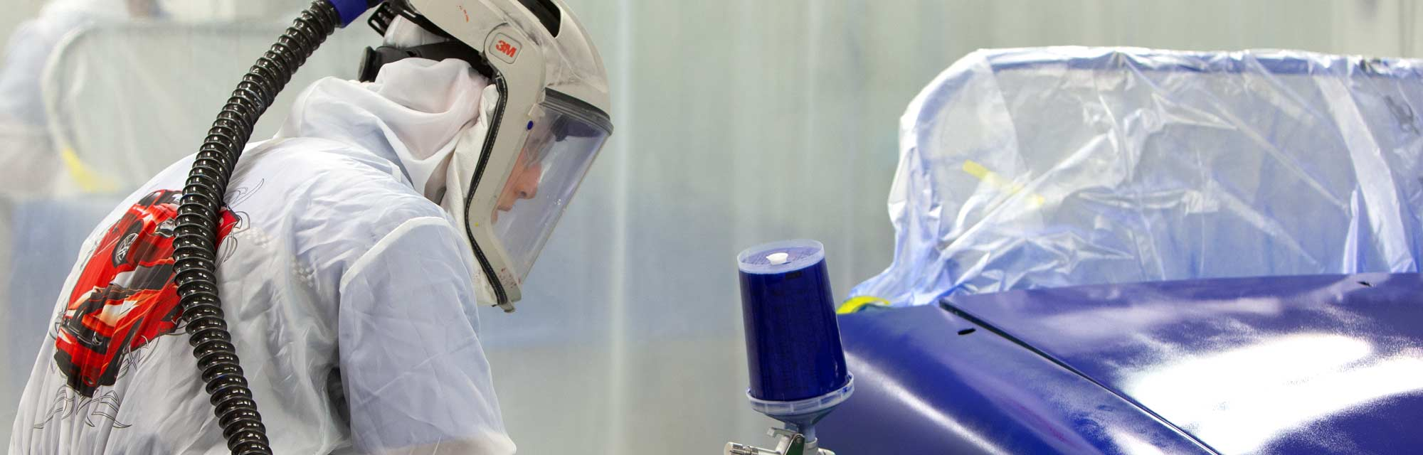 An image of a UTI student from the collision repair technician program painting a car