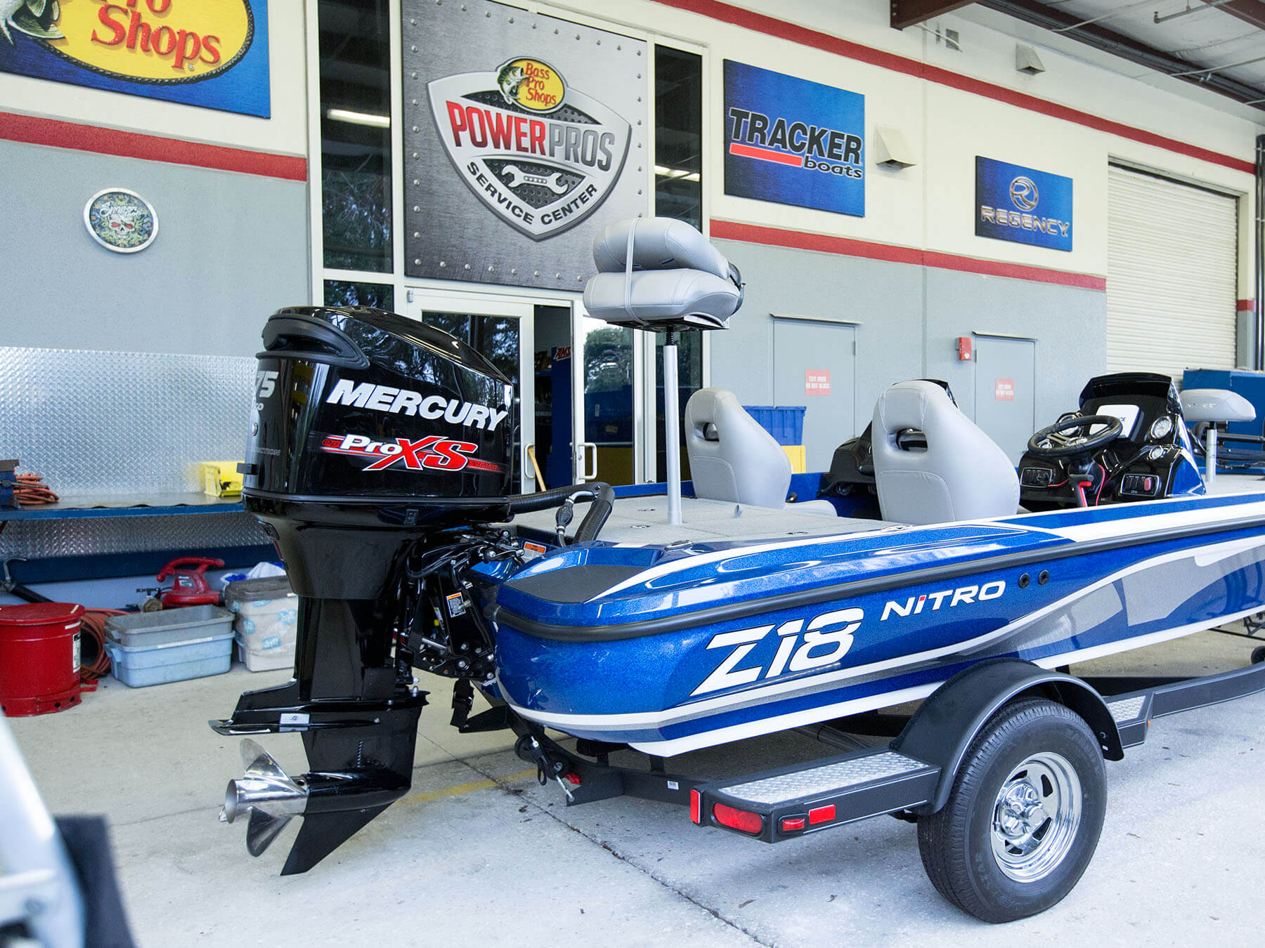 Blue z18 nitro boat with a mercury pro xs engine outside of the classroom