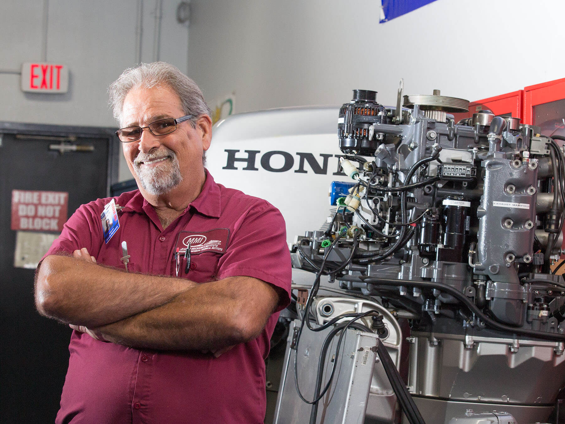 MMI instructor smiling next to a Honda marine engine