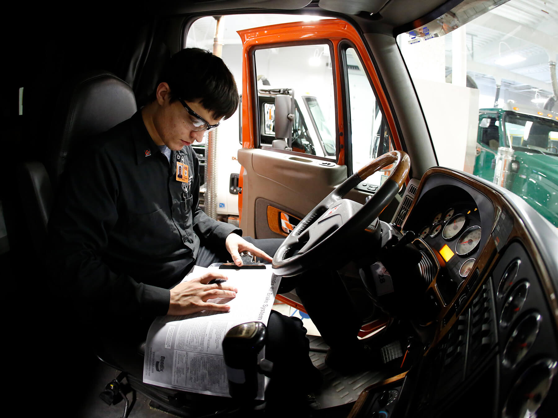 UTI student looking at a piece of paper inside a diesel truck