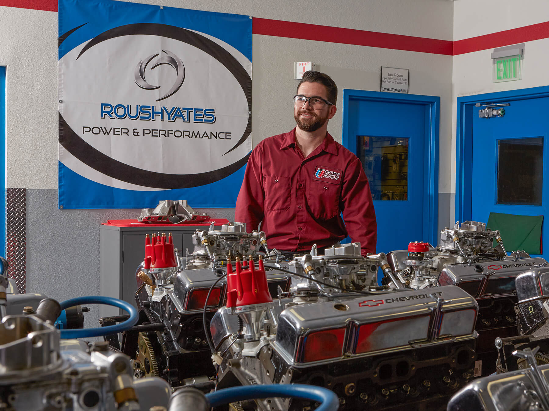 UTI instructor smiling in-front of Chevrolet engines at the Dallas campus