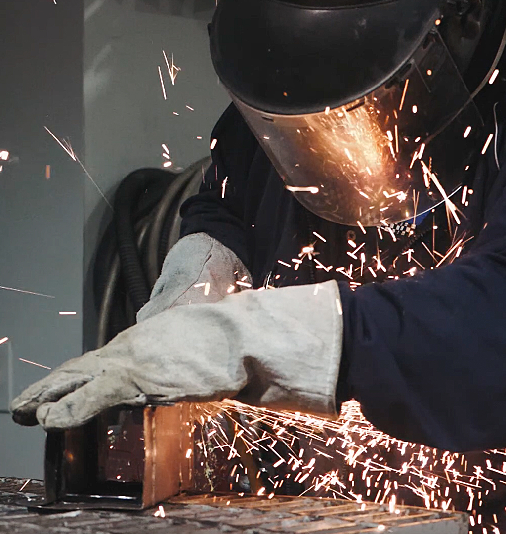 Close up of a collision repair student grinding down an object creating sparks