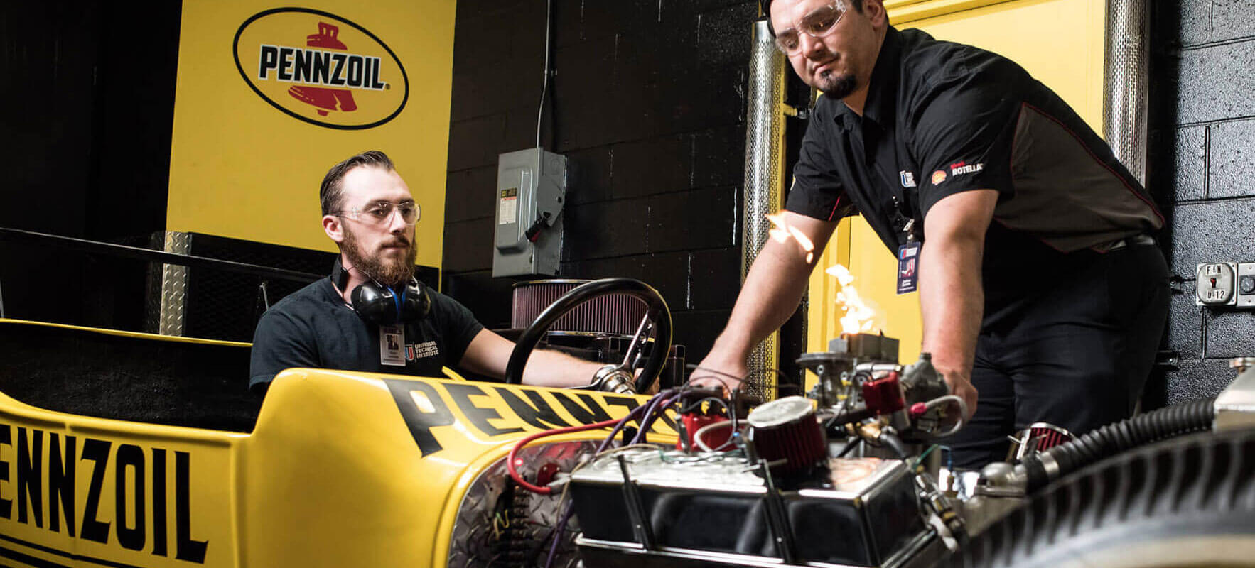 Students participating in UTI's Ignite program working on a car