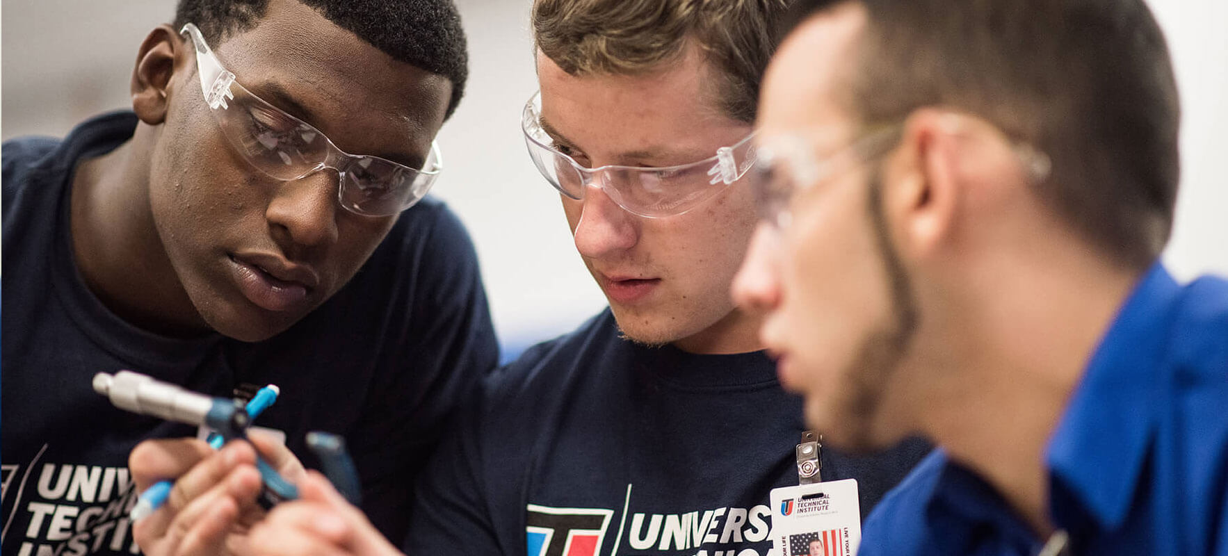 Three students working on automotive components at UTI's Ignite program