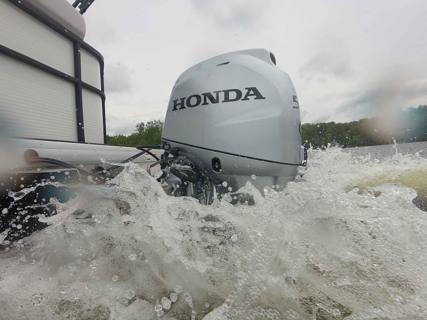 Action shot of Honda engine in the water making waves