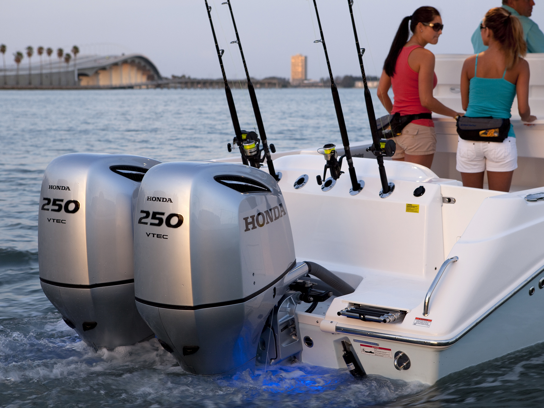 2 honda 250 vtec engines attached to the back of a white boat with fishing rods