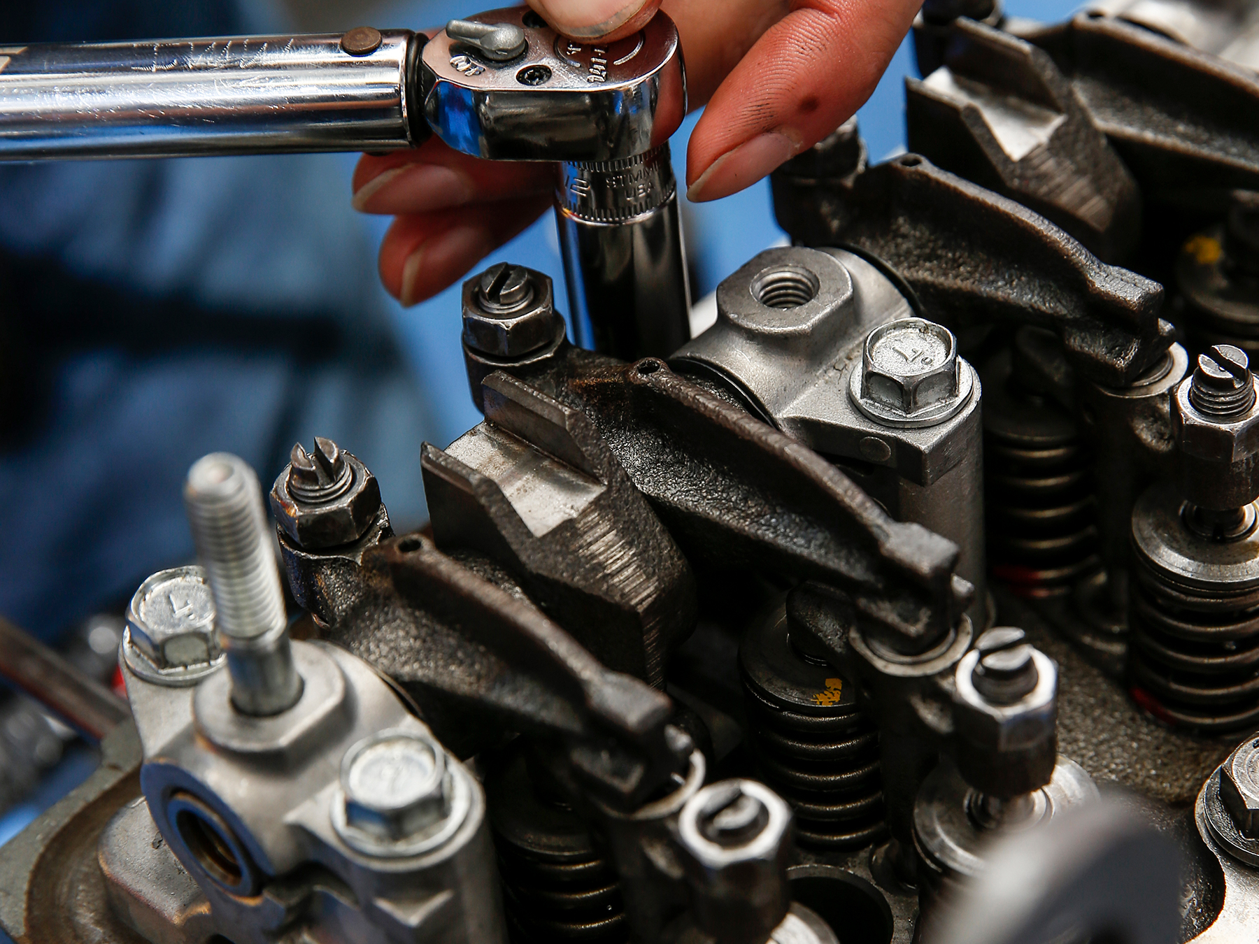 Extreme close-up of MMI student wrenching on an engine