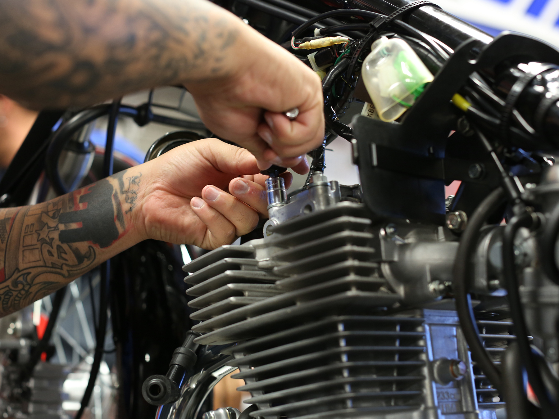 Close up of MMI student hands working on a motorcycle engine
