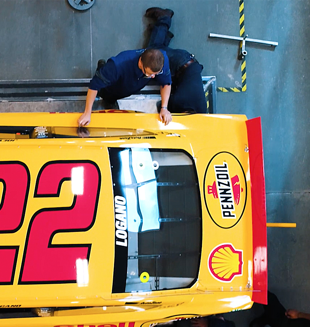 Overhead photo of nascar students working on a yellow Pennzoil nascar race car