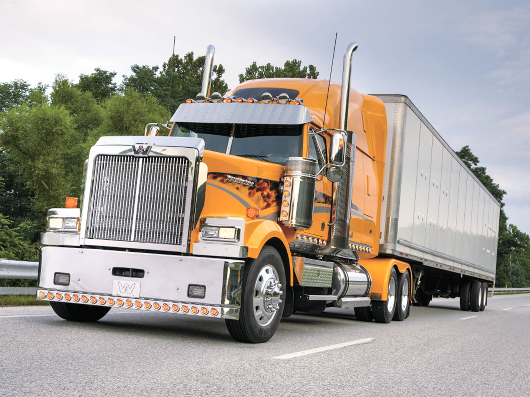 Yellow western star diesel truck driving on a highway