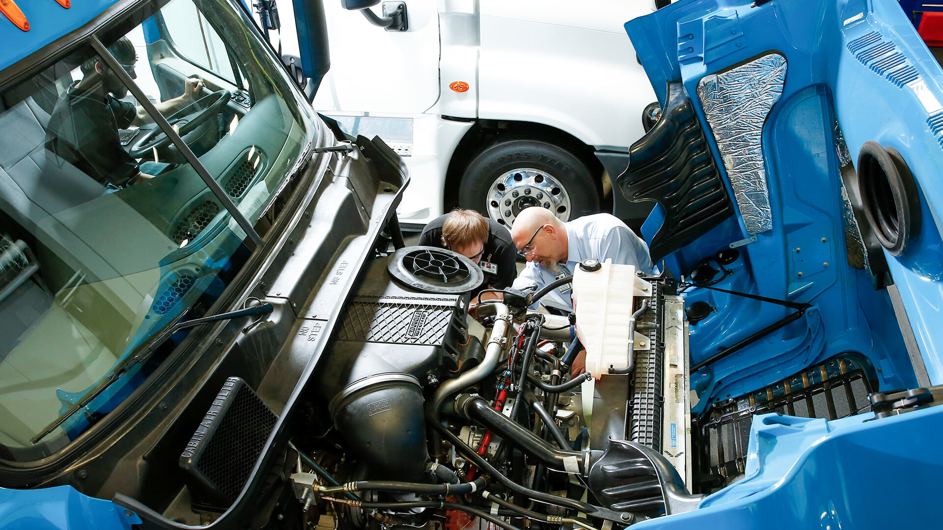 Overhead photo of an UTI instructor and student working on a freightliner diesel truck
